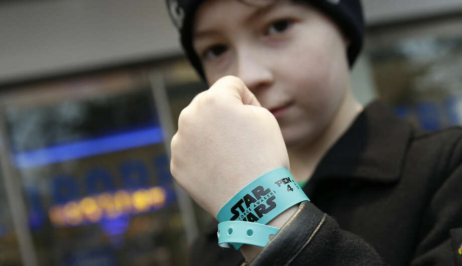 Josh Hobard holds up his coloured wrist band that will allow him entry to the fans area fro the European Premier of the new Star Wars film 'The Force Awakens' after collecting the band in London,Tuesday, Dec. 15, 2015, The film will have its European gala opening Wednesday. (AP Photo/Alastair Grant)