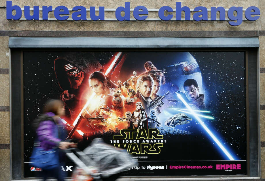 A woman pushes her children's buggy passed a poster for the new Star Wars film 'The Force Awakens' in Leicester Square London as preparations are made for the European Premiere of the new Star Wars film Tuesday, Dec. 15, 2015, the film will have its European gala opening Wednesday. (AP Photo/Alastair Grant)