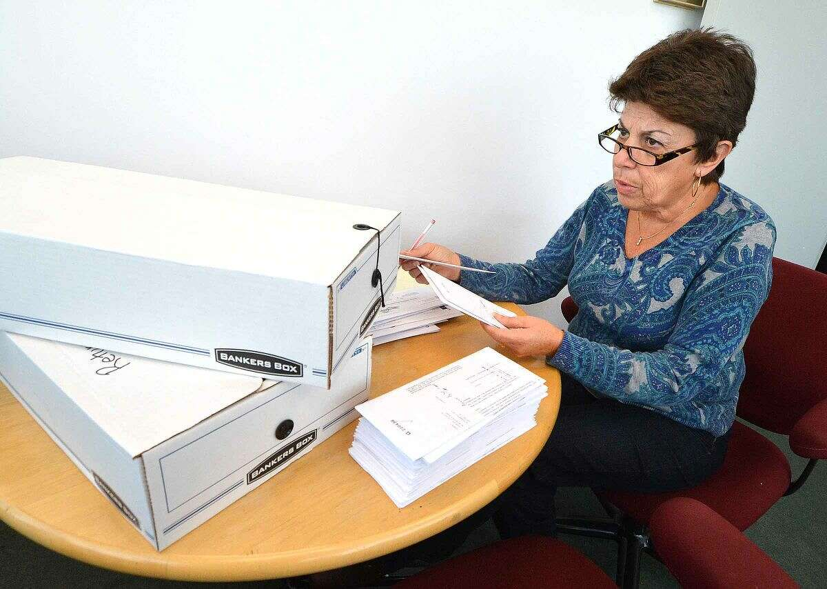 Lucille Limone reads voter information as absentee ballots are marked in the official poll books in the Stamford Registrar of Voters Office.