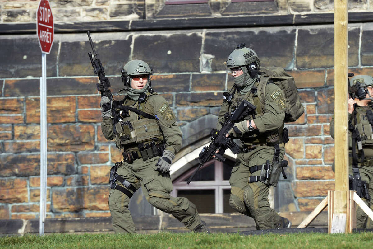 A Royal Canadian Mounted Police intervention team responds to a reported shooting at Parliament building in Ottawa, Wednesday, Oct. 22, 2014. A soldier standing guard at the National War Memorial has been shot by an unknown gunman and there have been reports of gunfire inside the halls of Parliament. (AP Photo/The Canadian Press, Adrian Wyld)