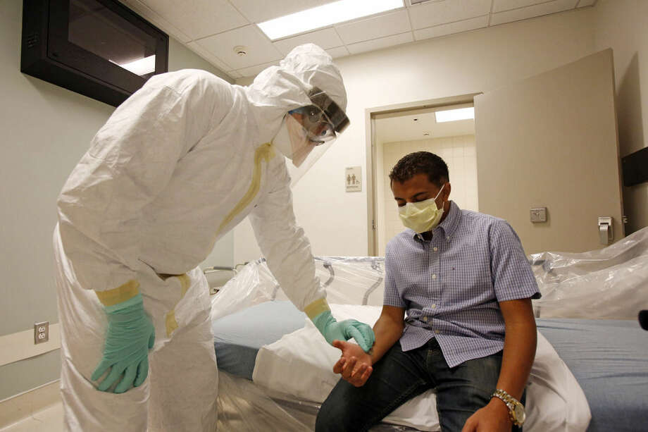 FILE- In this undated photo provided by the UCLA Health System, doctors and staff participate in a preparedness exercise on diagnosing and treating patients with Ebola virus symptoms, at the Ronald Reagan UCLA Medical Center in Los Angeles. The exercise was observed by Los Angeles County health department officials. (AP Photo/UCLA Health System, Reed Hutchinson, File)