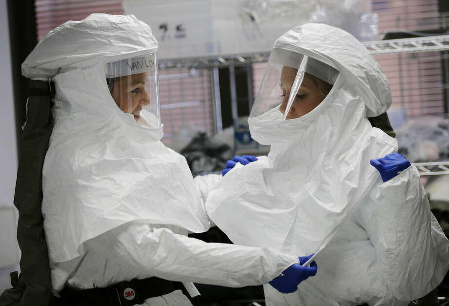 FILE- In this Oct. 24, 2014, file photo, members of the Department of Defense's Ebola Military Medical Support Team assist each other with their protective gear during training at San Antonio Military Medical Center in San Antonio. (AP Photo/Eric Gay, File)
