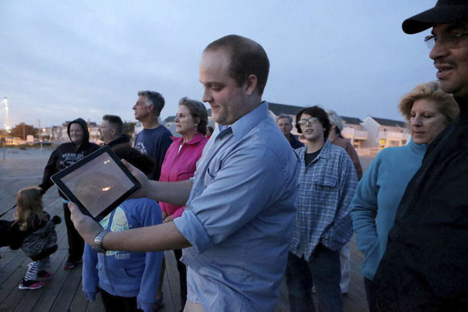 Dave Uhrich, an Ocean City High School physics teacher, center, holds a computer tablet as a gathering of people who were on the Ocean City Boardwalk, in Ocean City, NJ, to view a rocket launched from Virginia crashes after takeoff Tuesday, Oct., 27, 2014. The rocket was carrying supplies to the International Space Station and contained a science experiment created by the local high school students. (AP Photo/The Press of Atlantic City, Vernon Ogrodnek) MANDATORY CREDIT