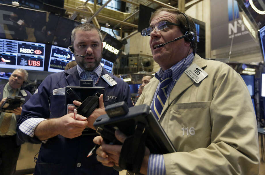 Traders Kevin Lodewick, left, and Jonathan Niles work on the floor of the New York Stock Exchange, Wednesday, Oct. 29, 2014. Major stock indexes traded in a tight range in the early going as investors wait for word from the Federal Reserve and mull over a mixed batch of earnings results. (AP Photo/Richard Drew)
