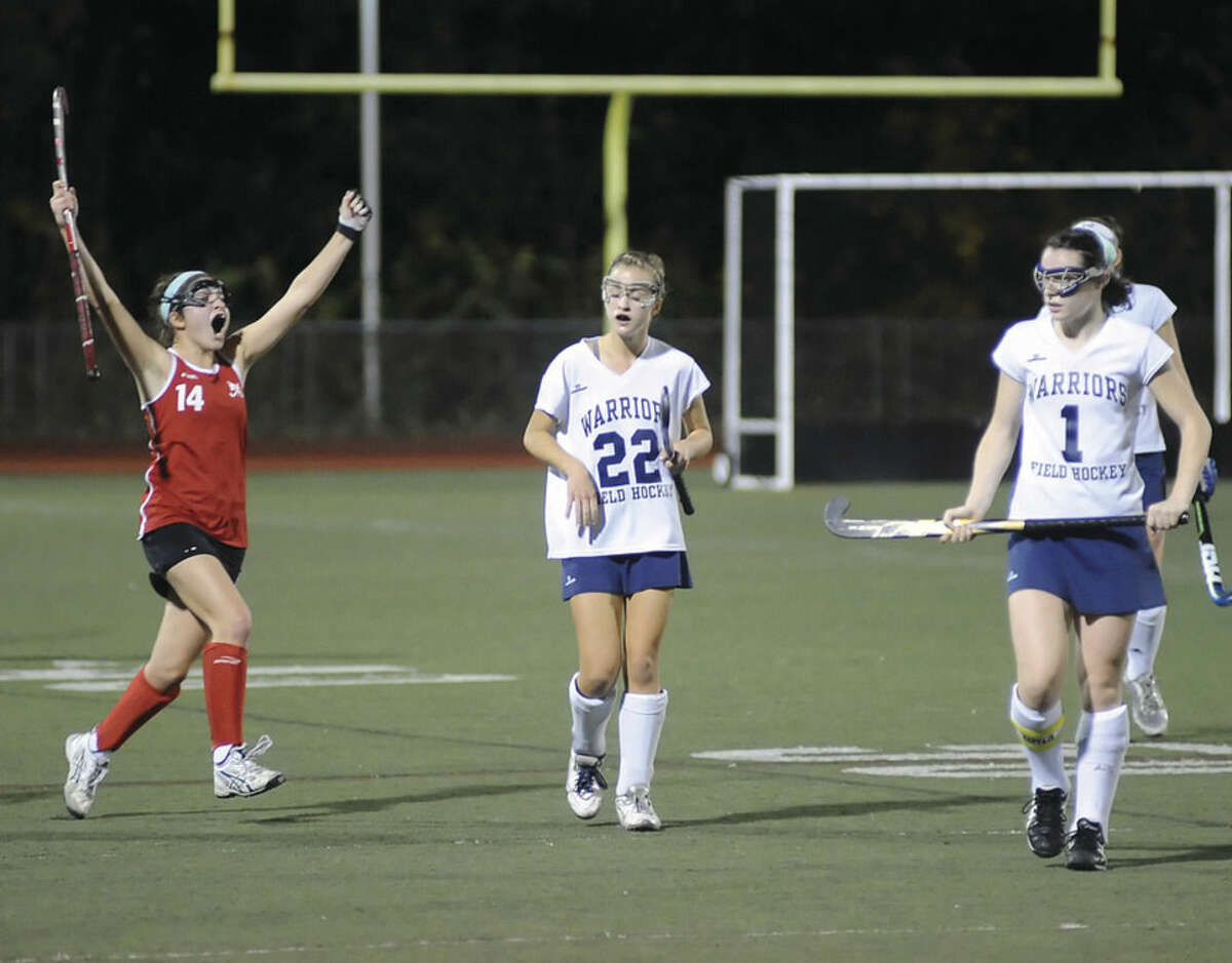Hour photo/John Nash New Canaan's Isabel Taban, left, celebrates the final buzzer in the Rams' 1-0 win over Wilton as Warrior players Maddie Duffy, center, and Megan Cunningham dejectedly walk off Casagrande Field in Norwalk during the FCIAC field hockey semifinals.