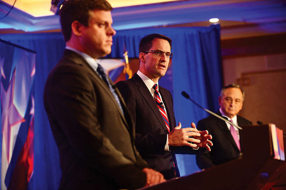 Hour photo / Erik Trautmann Connecticut Congressman Jim Himes, center, and GOP challenger Dan Debicella debate at the Norwalk INN Tuesday afternoon.