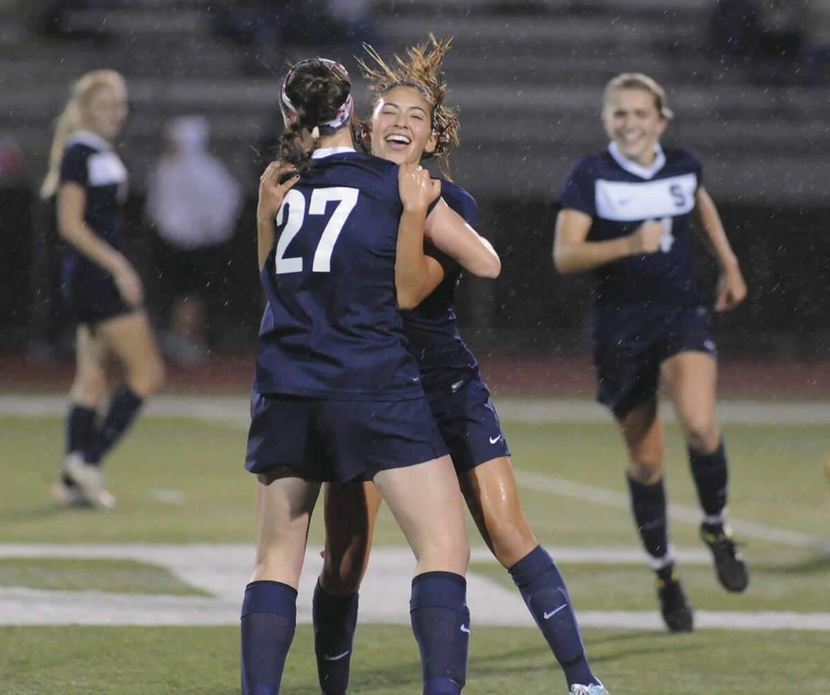 Hour photo/John Nash Staples' Lauren Garcia embraces tammate Charlotte Rossi (27) after scoring the game-tying goal in the 76th minute of Wednesday's FCIAC Girls Soccer Championship game at Testa Field in Norwalk. The game against Fairfield Warde finished in a 1-1 tie leaving the Wreckers and the Mustangs as co-champs. It was the first league title for both teams.