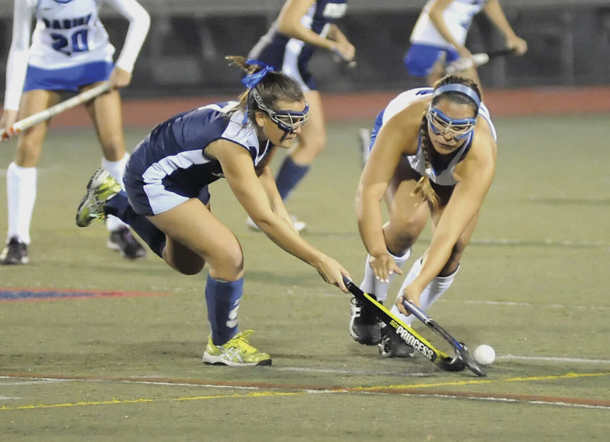 Hour photo/John Nash Staples' Meg Fay, left, lunges for the ball alongside Darien's Campbell Matheis during Tuesday's FCIAC field hockey semifinal at Casagrande Field in Norwalk.