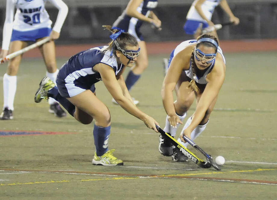 Hour photo/John NashStaples' Meg Fay, left, lunges for the ball alongside Darien's Campbell Matheis during Tuesday's FCIAC field hockey semifinal at Casagrande Field in Norwalk.