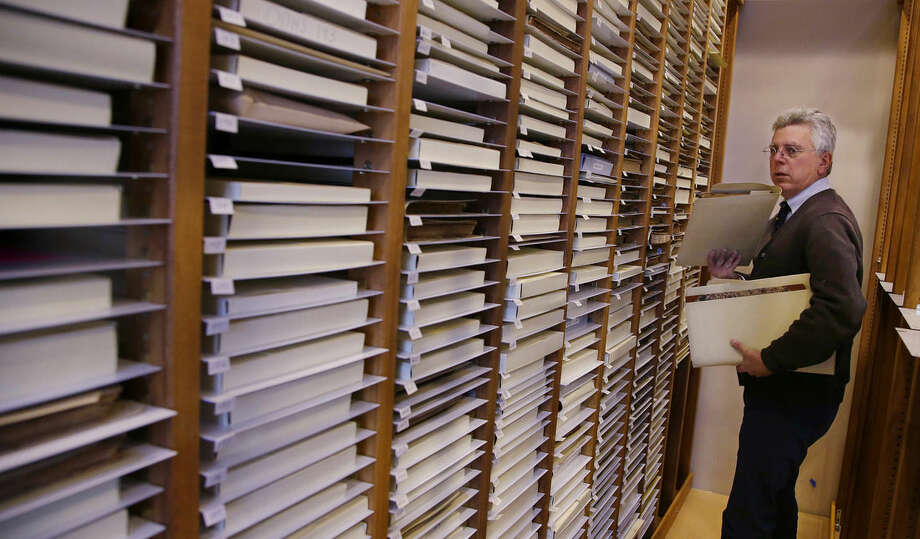 In this Tuesday, Dec. 8, 2015 photo, New Bedford Whaling Museum senior maritime historian Michael Dyer combs through the racks of whaling vessel log books in New Bedford, Mass. Maritime historians, climate scientists and ordinary citizens are coming together on a project to study 19th-century whaling ship logbooks to better understand modern-day climate change. The New Bedford Whaling Museum is transcribing and digitizing its logbooks as well as original data sources for this project, called Old Weather: Whaling. (AP Photo/Stephan Savoia)