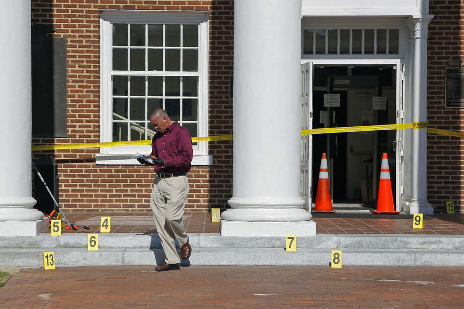 Crime scene investigator Larry Bryant with the Nash Co. Sheriff's Dept. gathers evidence from the courthouse steps after two people were shot in front of the Nash Co. Courthouse in Nashville N.C., Tuesday, Oct. 28, 2014. A manhunt involving helicopters and dozens of armed officers patrolling a nearby highway was underway for two men who Nash County Sheriff Dick Jenkins said fled in a white car. (AP Photo/The News & Observer, Chris Seward)