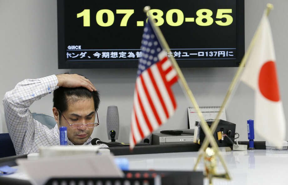 A money trader watches the monitor under a currency board updating real time Japanese yen rate against U.S. dollar at a foreign exchange brokerage in Tokyo, Tuesday, Oct. 28, 2014. Economists have plenty of quibbles, but many agree that the Federal Reserve accomplished the bulk of its goals with its bond-buying program, known as quantitative easing, or QE. The dollar has actually held up against most major currencies, as the euro and Japanese yen have slumped. (AP Photo/Shizuo Kambayashi)