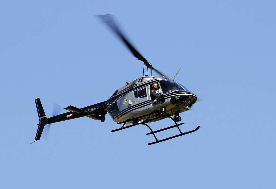 Police use a helicopter to look for two suspects after two people were shot in front of the Nash County courthouse in Nashville N.C. on Tuesday, Oct. 28, 2014. A manhunt involving helicopters and dozens of armed officers patrolling a nearby highway was underway for two men who Nash County Sheriff Dick Jenkins said fled in a white car. (AP Photo/The News & Observer, Chris Seward)