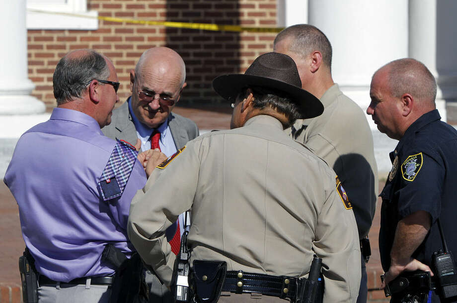 Nash County Sheriff Richard Jenkins, second from left, talks with other officers after two people were shot in front of the Nash County Courthouse in Nashville, N.C., on Tuesday, Oct. 28, 2014. A manhunt involving helicopters and dozens of armed officers patrolling a nearby highway was underway for two men who Jenkins said fled in a white car. (AP Photo/The News & Observer, Chris Seward)