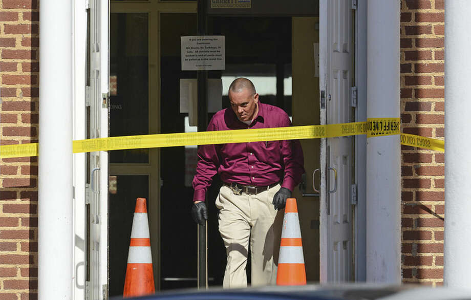 A crime scene investigator from the Nash County Sheriff's Office works a crime scene at the Nash County Courthouse Tuesday, Oct. 28, 2014 after officials say a gunman shot two people earlier in the day. A manhunt is on for two suspects in the shooting of two men outside a the courthouse Tuesday, authorities said. (AP Photo/The Wilson Times, Brad Coville)