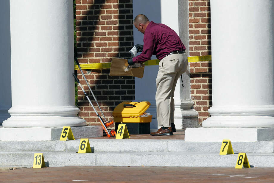 Crime scene investigator Larry Bryant with the Nash Co. Sheriff's Dept. gathers evidence from the courthouse steps after two people were shot in front of the Nash Co. Courthouse in Nashville, N.C. on Tuesday, Oct. 28, 2014. A manhunt involving helicopters and dozens of armed officers patrolling a nearby highway was underway for two men who Nash County Sheriff Dick Jenkins said fled in a white car. (AP Photo/The News & Observer, Chris Seward)