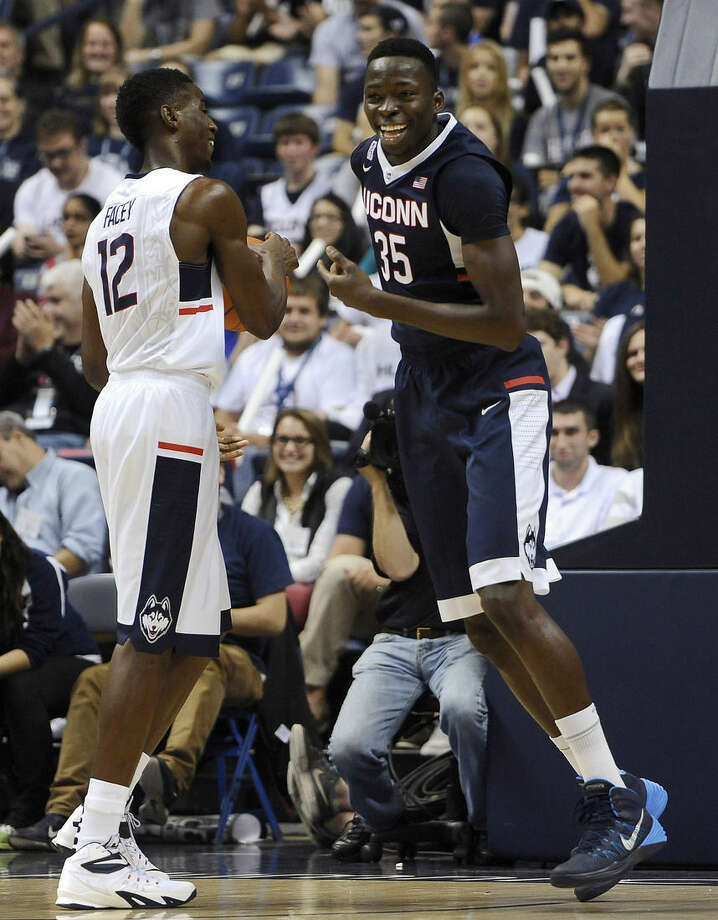 In this Oct. 17, 2014 photo, Connecticut's Amida Brimah, right, smiles as he passes Kentan Facey, left, after scoring a basket at the men's and women's NCAA basketball teams' First Night event in Storrs, Conn. UConn will host Bryant to open the 2014-15 season on Friday, Nov. 14. (AP Photo/Jessica Hill)