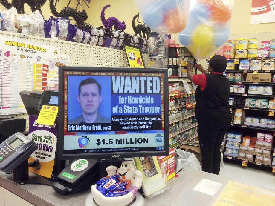 FILE - In this Sept. 20, 2014, file photo, a wanted advertisement for Eric Frein is displayed at a grocery store in Philadelphia. Authorities said Thursday, Oct. 30, 2014, that they have captured Frein, who had been eluding police, but is charged with killing one Pennsylvania State Trooper and seriously wounding another in a late night ambush. (AP Photo/Matt Rourke, File)