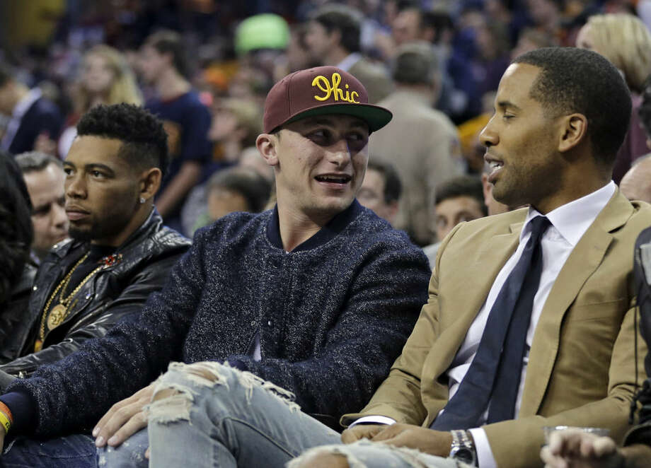Cleveland Browns quarterback Johnny Manziel, center, talks to a seatmate in the first half of an NBA basketball game between the New York Knicks and the Cleveland Cavaliers, Thursday, Oct. 30, 2014, in Cleveland. (AP Photo/Tony Dejak)