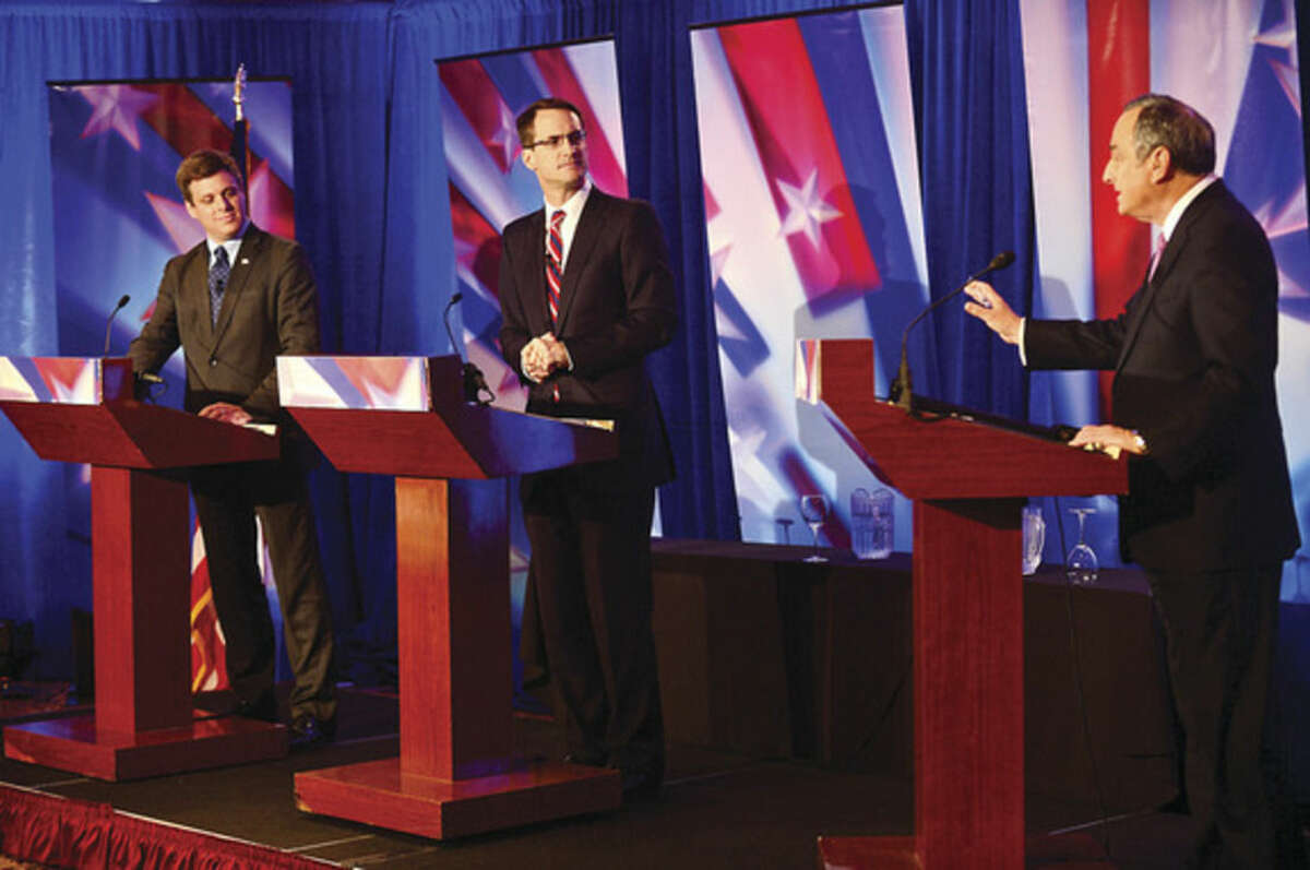 Hour photo / Erik Trautmann News 12 News Director Tom Appleby, right, moderates the debate between U.S. Rep. Jim Himes, center, and GOP challenger Dan Debicella, left, at the Norwalk Inn Tuesday afternoon.