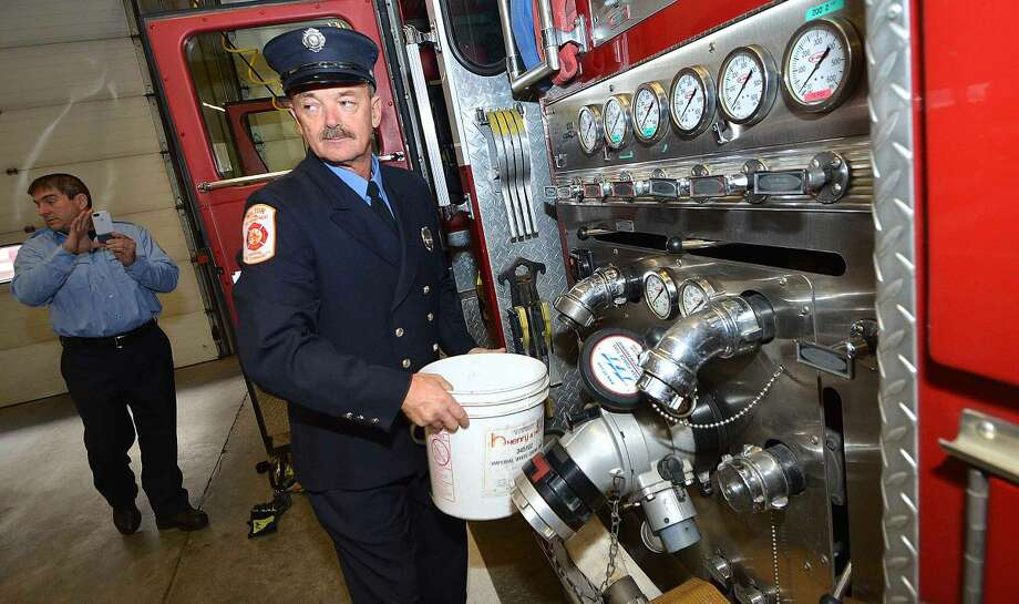 Apparatus Supervisor Ralph Nathanson fills some water from the old Truck 4 to be placed into the new truck 4, a department tradition at Wilton Fire Headquarters.