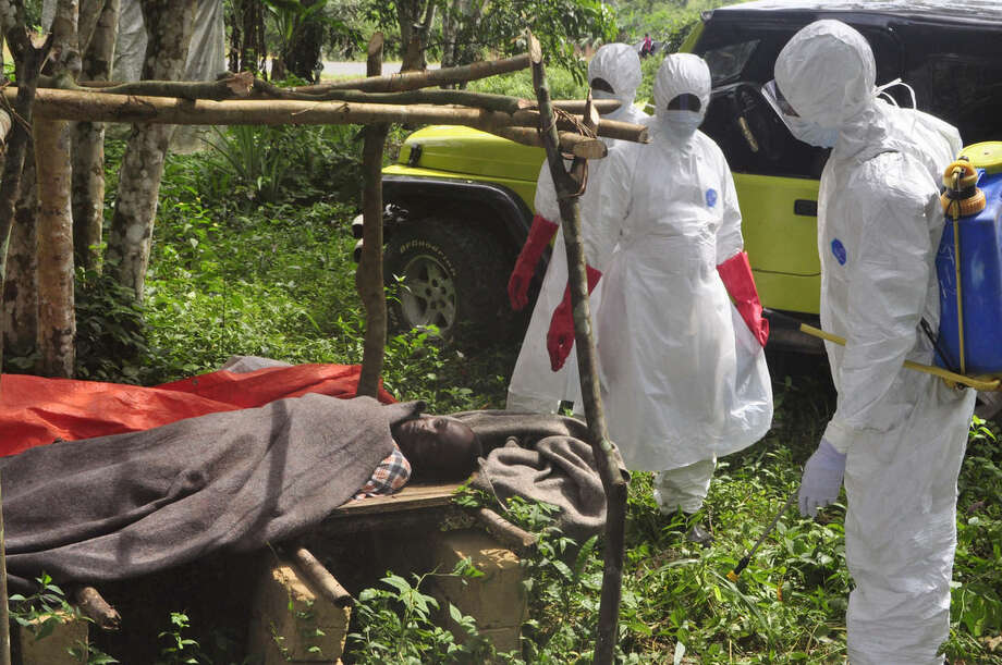 Hearth workers spray disinfectant around a man suspected of dying from the Ebola virus on the outskirts of Monrovia, Liberia, Friday, Oct. 31, 2014. The World Health Organization said this week that the rate of infection in Liberia appears to be falling but warned that the response effort must be kept up or the trend could be reversed. (AP Photo/ Abbas Dulleh)