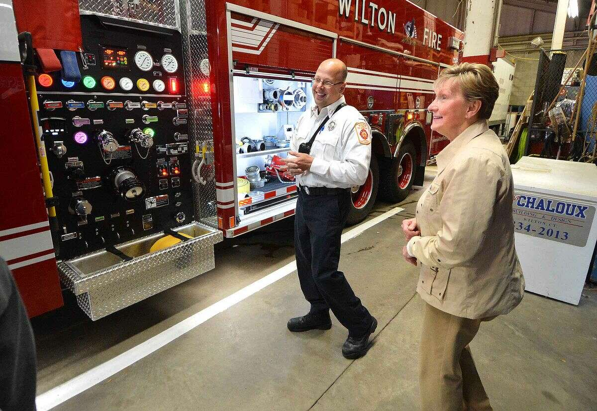 Fire Capt. Kevin Czarnecki shows the town of Wilton's CFO Sandy Dennies the controls on the towns new Engine-Tanker 4 after a ceremony at headquarters.
