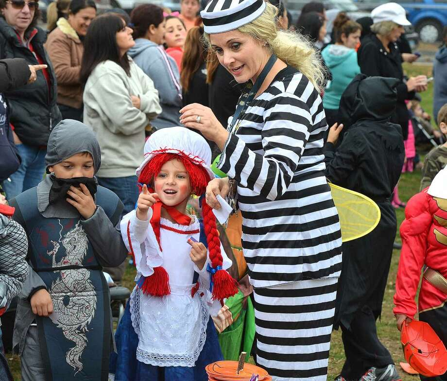 Hour Photo/Alex von Kleydorff Teacher Jen Sweeters helps 1st grader Kayla Barta as Raggedy Ann vote for her favorite pumpkin during Brookside School's Halloween parade