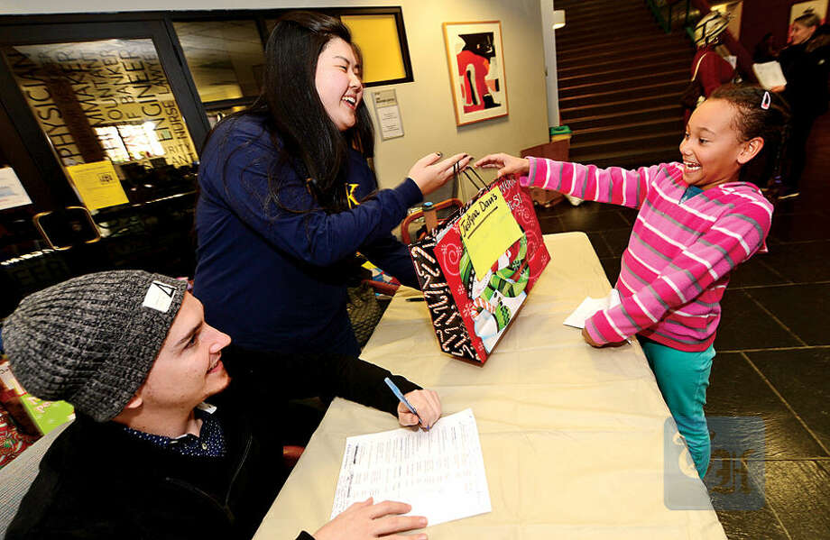 Hour photo / Erik Trautmann Phi Theta Kappa Alpha Iota Nu Honor Society members Fernado Alves and Natassia Tanaka give out Christmas gifts to 7 year old Naomi Davis during the 1st annual Phi Theta Kappa Honor Society Winterfest at Norwalk Community College Saturday.
