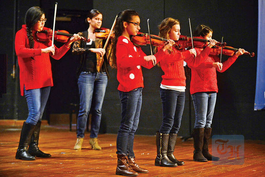 Hour photo / Erik Trautmann Vilonists Sydenet Hurtado, Alyssa da Silva, Carolina Rychlik and Erika Silveira, are accompanied by Ingrid Magalhaes, Vice President of Service, Phi Theta Kappa, Alpha Iota Nu, in a musical performance during the 1st annual Phi Theta Kappa Honor Society Winterfest at Norwalk Community College Saturday.
