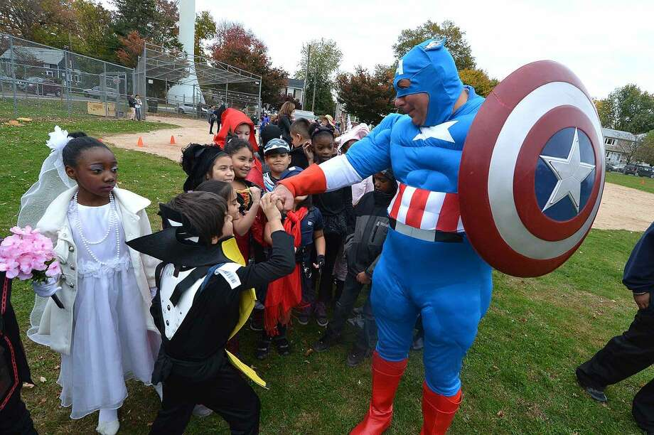 Hour Photo/Alex von Kleydorff Gym Teacher Tim Downey gets some fist bumps as Captain America during the Brookside School Halloween costume parade on Friday