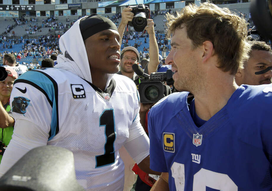 FILE - In this Sept. 22, 2013, file photo, Carolina Panthers' Cam Newton (1) greets New York Giants' Eli Manning (10) after an NFL football game in Charlotte, N.C. The Panthers (13-0) play the New York Giants (6-7) on Sunday, Dec. 20, 2015, in East Rutherford, N.J. (AP Photo/Bob Leverone, File)