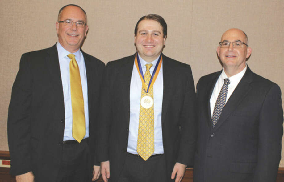 Contributed photoFrom left, Mark A. Thompson, executive vice president and provost at Quinnipiac University; Ted Koly; and Matthew O'Connor, dean of the School of Business and Engineering. Koly has received the 2015 Recent Alumni Award from Quinnipiac University.