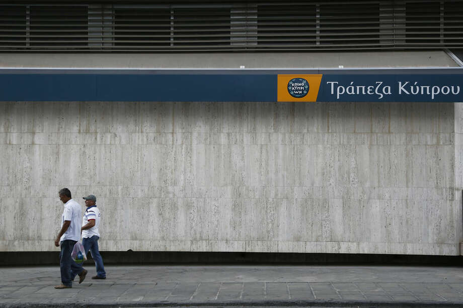 Men walk outside of a branch of Bank of Cyprus in central Nicosia, Cyprus, Sunday, Oct. 26, 2014. The European Central Bank says 13 of Europe's 130 biggest banks have flunked an in-depth review of their finances and must increase their capital buffers against losses by 10 billion euros ($12.5 billion). The Cypriot Hellenic bank is one of the 13 banks in Europe with the shortfall. (AP Photo/Petros Karadjias)