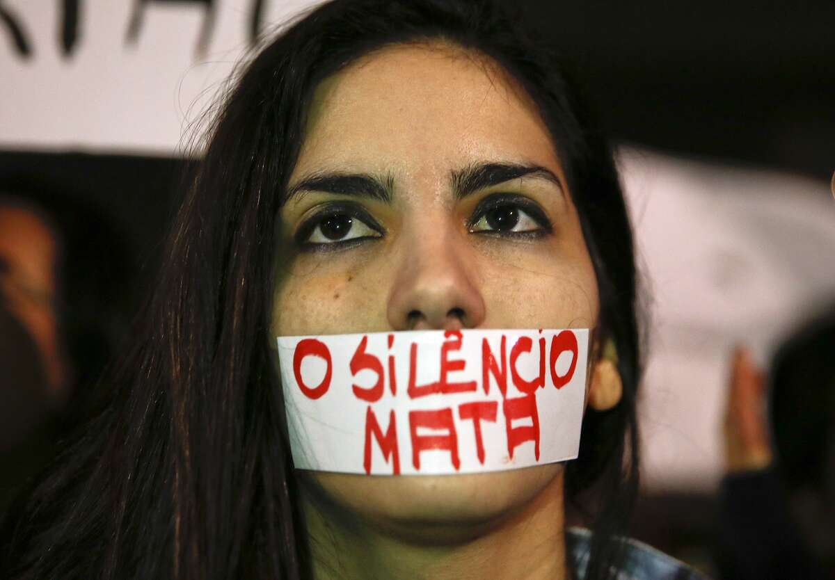 A woman with a piece of tape over mouth with a message that reads in Portuguese;