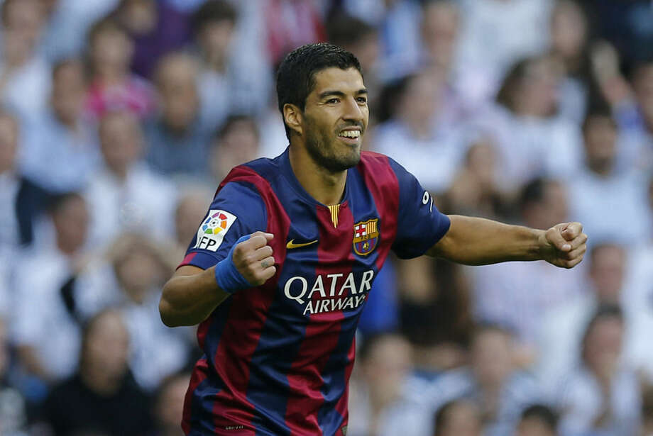 Barcelona's Luis Suarez celebrates after Barcelona's Lionel Messi scored during a Spanish La Liga soccer match between Real Madrid and Barcelona at the Santiago Bernabeu stadium in Madrid, Spain, Saturday Oct. 25, 2014. (AP Photo/
