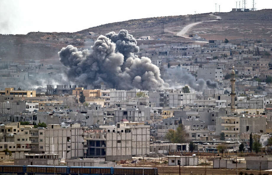 Smoke rises above the Syrian town of Kobani after an airstrike by the US led coalition, seen from a hilltop on the outskirts of Suruc, Turkey, near the Turkey-Syria border, Sunday, Oct. 26, 2014. Kobani, also known as Ayn Arab, and its surrounding areas, has been under assault by extremists of the Islamic State group since mid-September and is being defended by Kurdish fighters. (AP Photo/Vadim Ghirda)