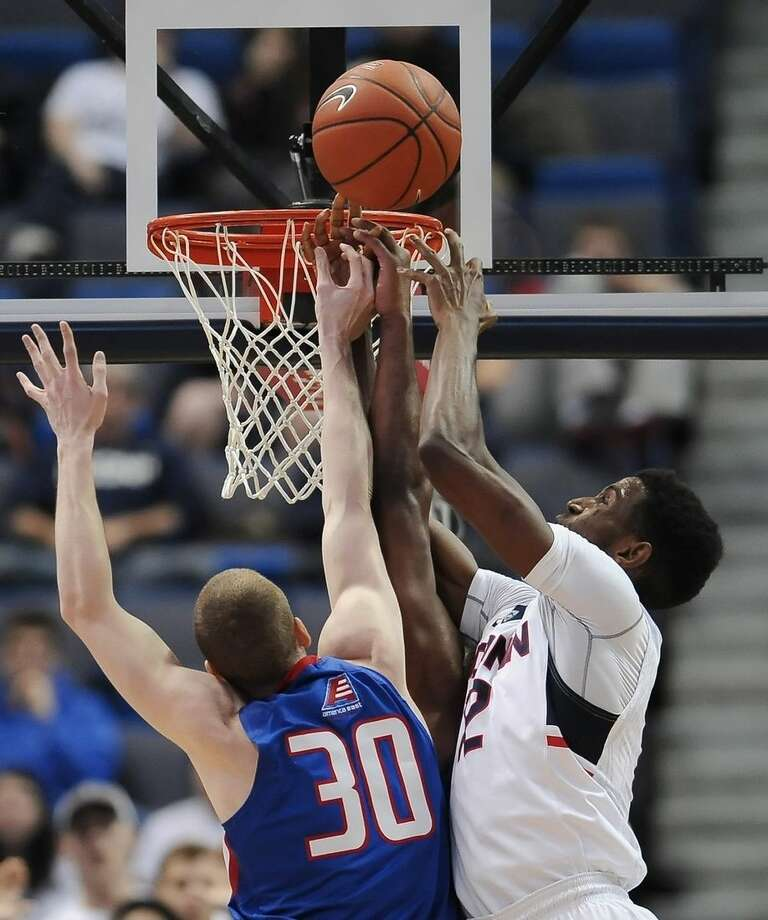 Connecticut's Kentan Facey, right, reaches up to stop a shot-attempt by UMass-Lowell's Mark Cornelius, left, in the first half of an NCAA college basketball game, Sunday, Dec. 20, 2015, in Hartford, Conn. (AP Photo/Jessica Hill)