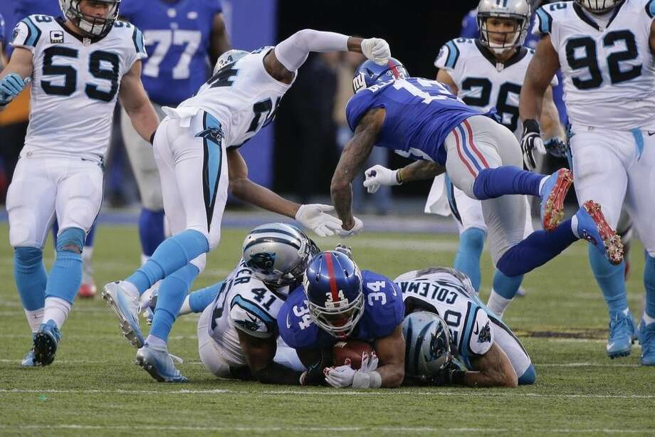 New York Giants' Odell Beckham (13) hits Carolina Panthers' Josh Norman (24) after teammate Shane Vereen (34) is tackled by Kurt Coleman (20) and Roman Harper (41) during the second half of an NFL football game Sunday, Dec. 20, 2015, in East Rutherford, N.J. (AP Photo/Julie Jacobson)