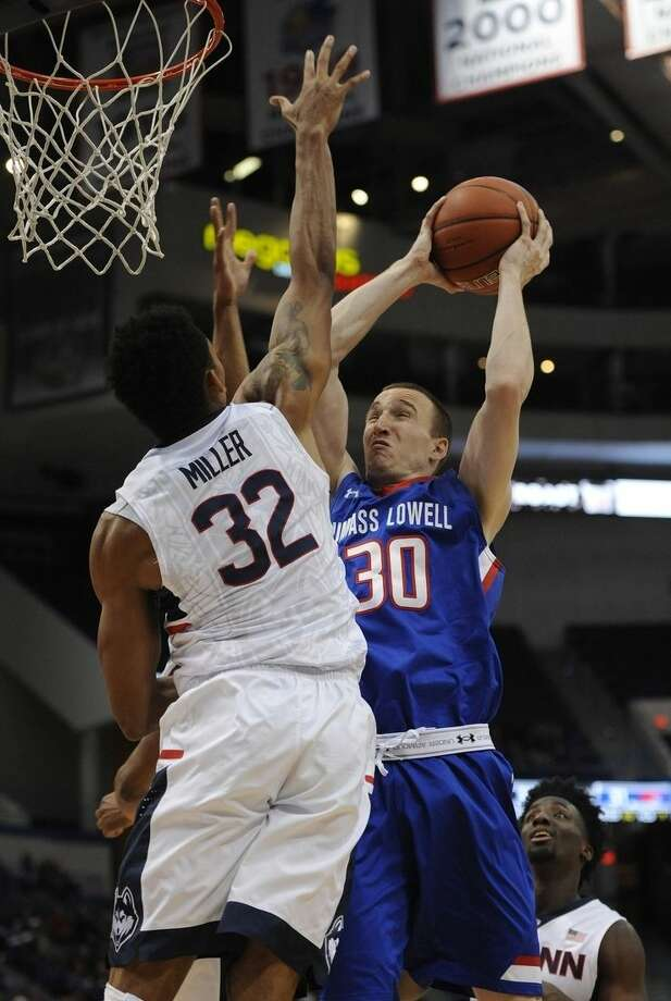 UMass-Lowell's Mark Cornelius, right, shoots as Connecticut's Shonn Miller, left, defends, in the first half of an NCAA college basketball game, Sunday, Dec. 20, 2015, in Hartford, Conn. (AP Photo/Jessica Hill)