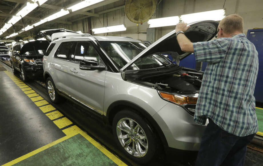In this Oct. 22, 2015, photo, workers perform final inspections on 2015 Ford Explorers on the assembly line at the Chicago Ford Assembly Plant. The seven-passenger Ford Explorer, introduced in the 1991 model year, was the first SUV that was equally at home navigating mountain trails or grocery store parking lots, says Karl Brauer, a senior analyst with the car buying site Kelley Blue Book. (AP Photo/M. Spencer Green)