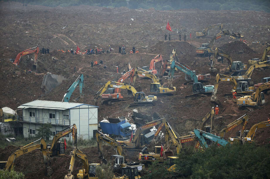 Rescuers use machinery to search for potential survivors following a landslide in Shenzhen, in south China's Guangdong province, Monday, Dec. 21, 2015. A mountain of excavated soil and construction waste buried dozens of buildings when it swept through an industrial park Sunday. (AP Photo/Andy Wong)