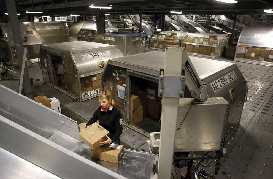 In this Nov. 20, 2015 photo, Rachel Fryer prepares to place a package inside a container behind her at Worldport in Louisville, Ky. Each container typically holds about 400 packages. (AP Photo/Patrick Semansky)