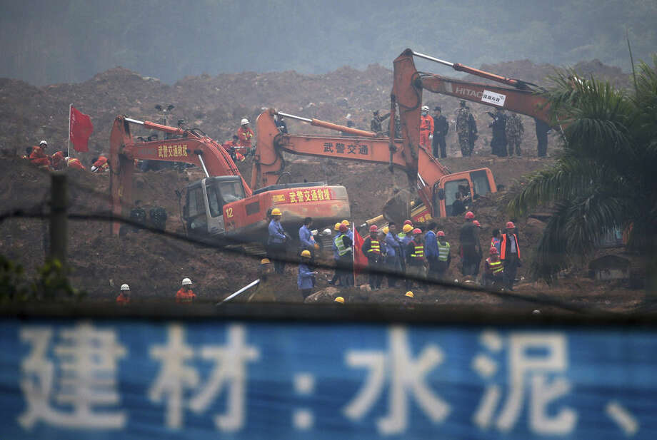 Rescuers search for potential survivors following a landslide in Shenzhen, in south China's Guangdong province, Monday, Dec. 21, 2015. A mountain of excavated soil and construction waste buried dozens of buildings when it swept through an industrial park Sunday. (AP Photo/Andy Wong)