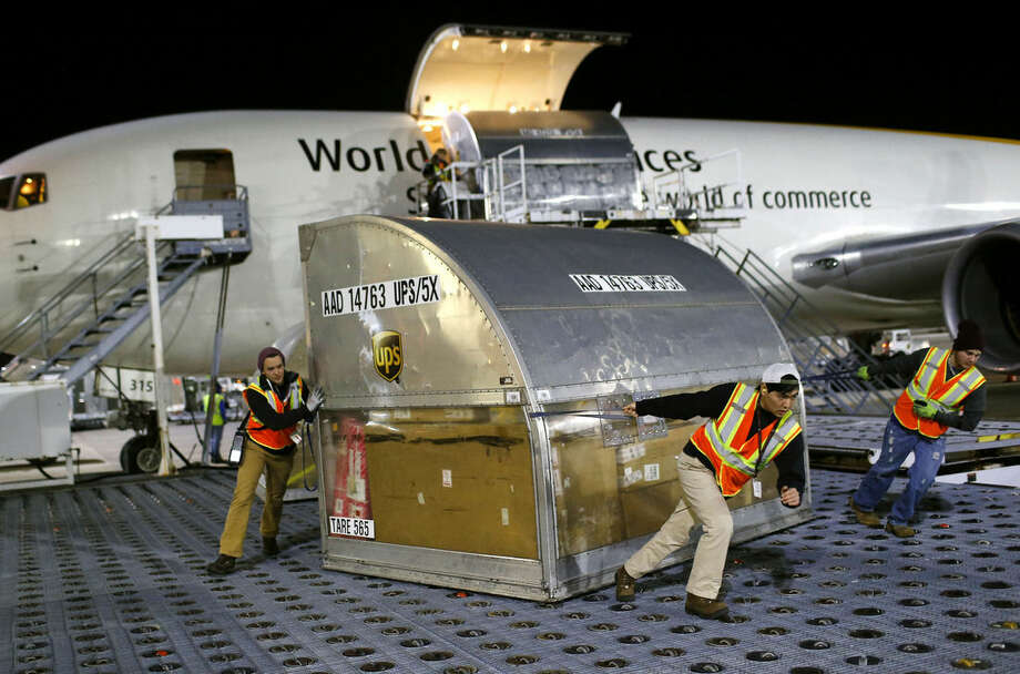 In this Nov. 20, 2015 photo, UPS workers guide a container across a floor containing casters after it was unloaded from an airplane at Worldport in Louisville, Ky. (AP Photo/Patrick Semansky)