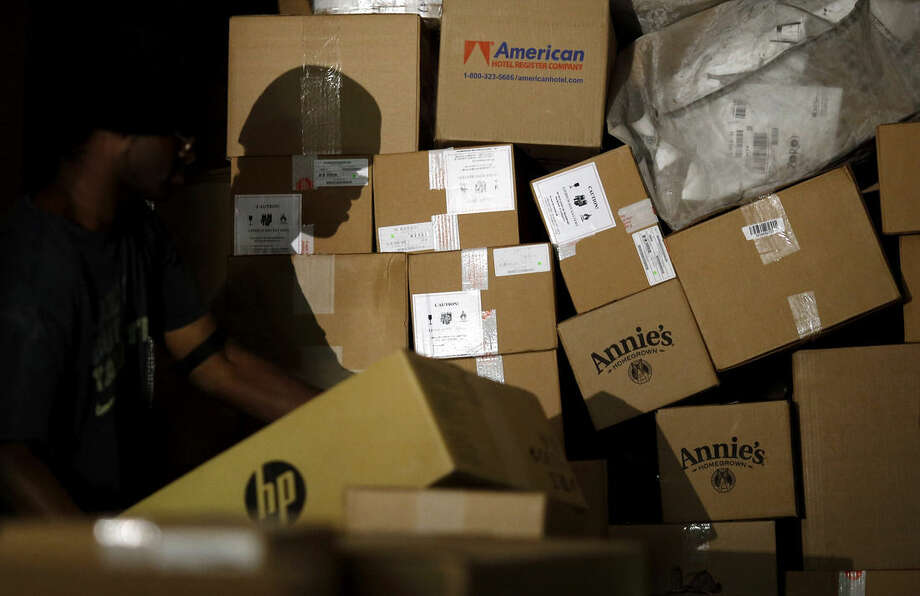 In this Nov. 20, 2015 photo, a worker's shadow is cast against boxes as he unloads them from a truck trailer at Worldport in Louisville, Ky. UPS and FedEx have been working with major retailers to hone their forecasts and have tailored their extra holiday workers to better meet the shipping spikes right after Thanksgiving and the weekend before Christmas. (AP Photo/Patrick Semansky)