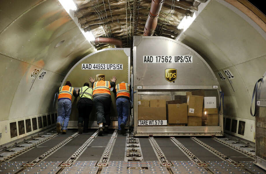 In this Nov. 20, 2015 photo, UPS workers push a container full of packages into place inside an airplane at Worldport in Louisville, Ky. In a five hour period at Worldport, 130 planes have landed, unloaded, reloaded and returned to the skies. (AP Photo/Patrick Semansky)