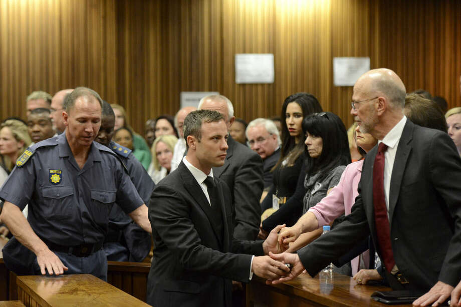 Oscar Pistorius, center, greets his uncle Arnold Pistorius, right, and other family members as he is led down to the cells of the court in Pretoria, South Africa, Tuesday, Oct. 21, 2014. Pistorius received a five-year prison sentence for culpable homicide by judge Thokozile Masipais for the killing of his girlfriend Reeva Steenkamp last year (AP Photo/Herman Verwey, Pool)