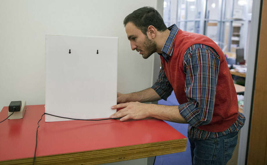 In this Nov. 19, 2015, photo, Massachusetts Institute of Technology researcher Fadel Adib sets up the RF-Capture device behind a wall in a room at MIT in Cambridge, Mass. RF-Capture uses WiFi signals to see through walls, and is able to sense where a person is in a room, if a person is sitting, moving or has fallen. It also can sense heart rate and breathing rate. (AP Photo/Scott Eisen)