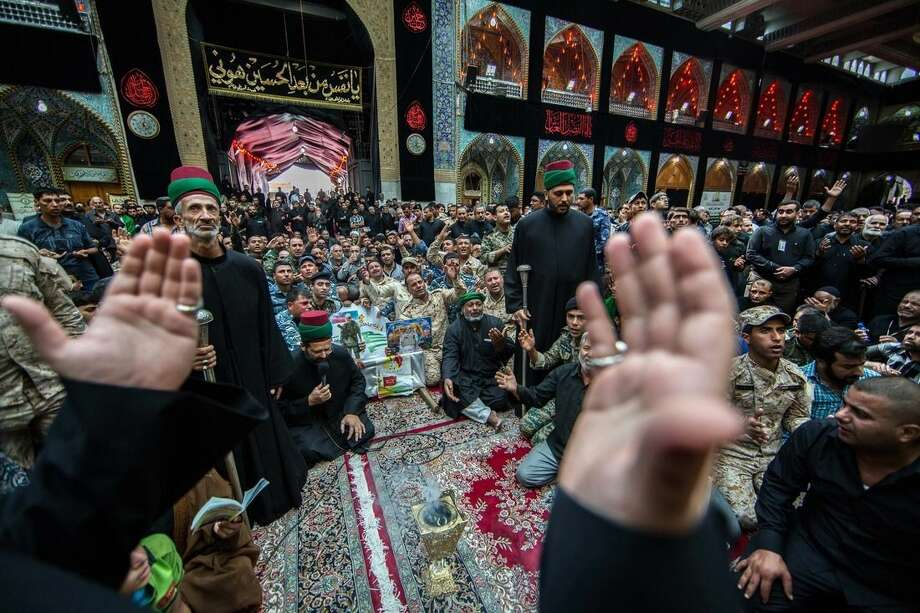 Members pray over the coffins of members of Iraq's Special Weapons and Tactics Team (SWAT) and Shiite militiamen during their funeral procession inside the holy Shiite shrine of Imam Hussein in the Shiite holy city of Karbala, 50 miles (80 kilometers) south of Baghdad, Iraq, Monday, Oct. 27, 2014. A suicide car bomber driving a military Humvee struck a checkpoint manned by Iraqi troops and pro-government Shiite militiamen in the Sunni town of Jurf al-Sakhar south of Baghdad on Monday, killing at least 24 people, officials said. (AP Photo/Ahmed al-Husseini)